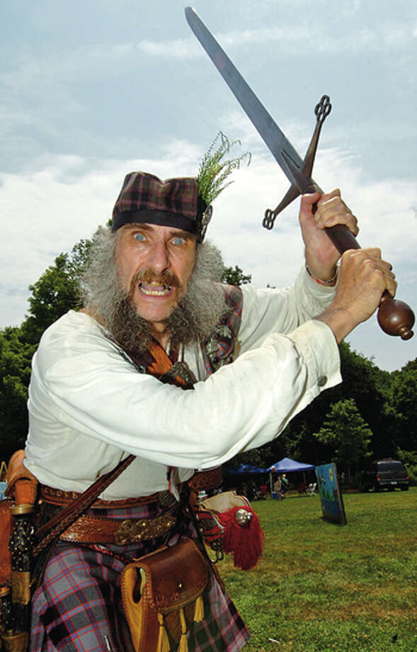 Angus McPherson brandishes a Claymore replica during the Round Hill Highland Games at Cranbury Park Saturday. Hour photo / Erik Trautmann / (C)2012, The Hour Newspapers, all rights reserved