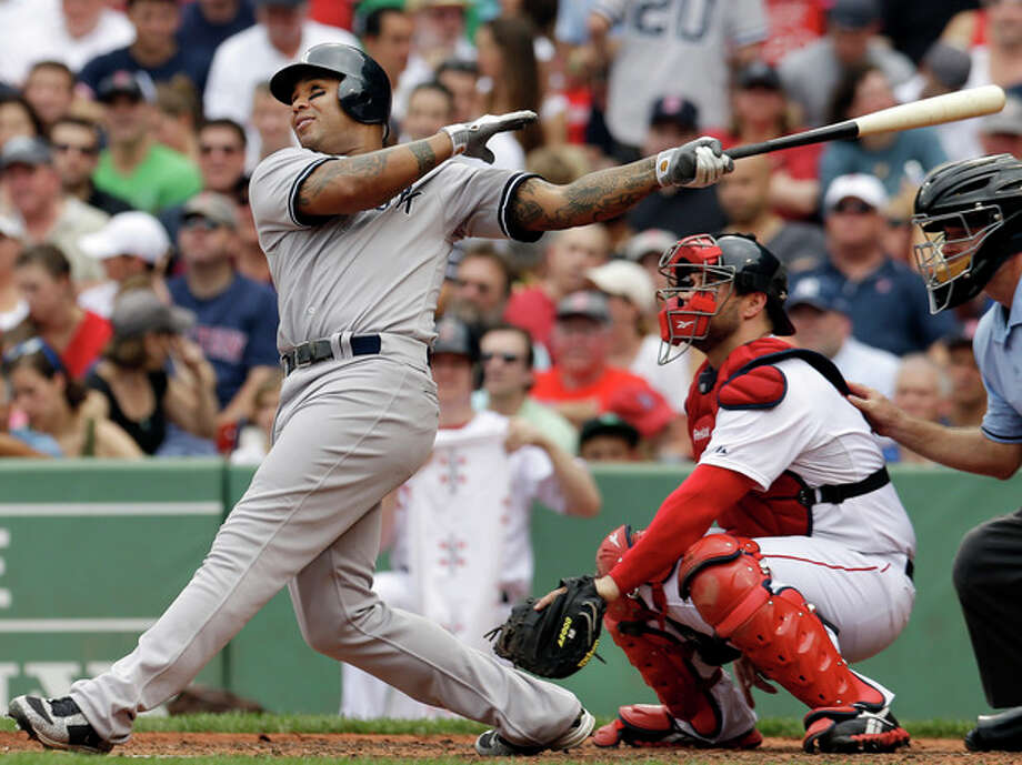 New York Yankees' Andruw Jones follows through on a solo home run as Boston Red Sox catcher Kelly Shoppach watches in the fourth inning of the first baseball game in a day-night doubleheader at Fenway Park in Boston Saturday, July 7, 2012. (AP Photo/Elise Amendola) / AP