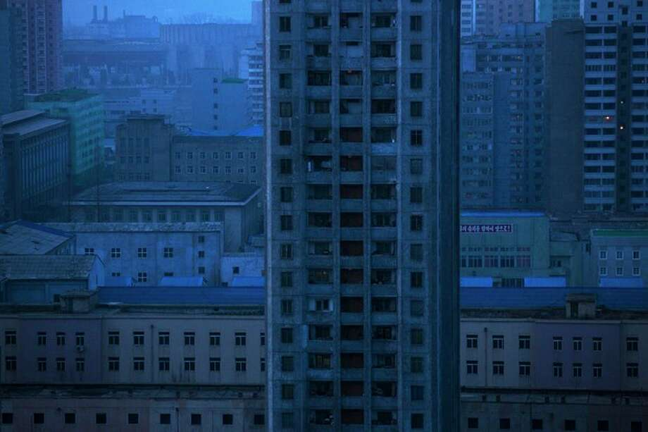 An apartment block stands among the buildings at dawn in central Pyongyang, North Korea, Wednesday, April 10, 2013. (AP Photo/David Guttenfelder) / AP