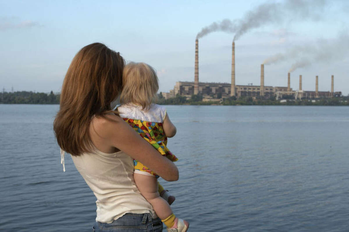 Young mother with her kids are looking at the chimney-stalks polluting an air