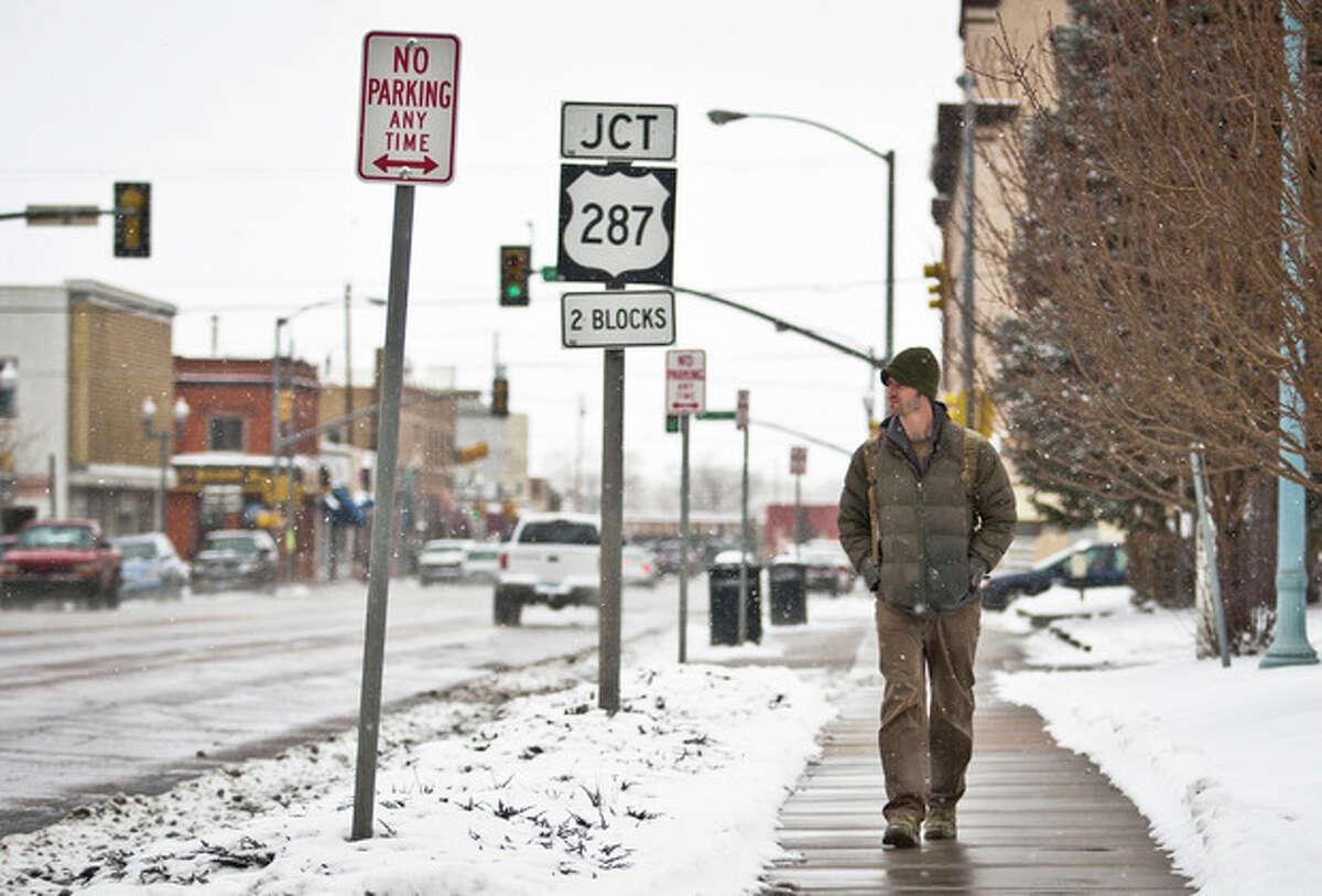 Laramie resident Leeds Butler walks down the sidewalk along Grand Avenue during an early afternoon snowfall in Laramie, Wyo., Tuesday, April 9, 2013. (AP Photo/Laramie Boomerang, Jeremy Martin)