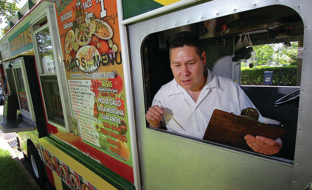 Hour photo / Alex von Kleydorff Owner Gil Hurtado takes an order at his Taqueria Las Salsas truck on The Green in Norwalk.