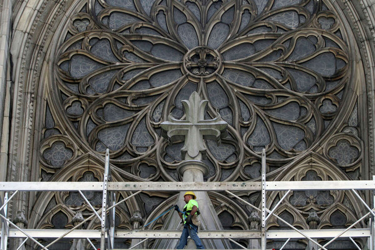 In this Tuesday, July 3, 2012 photo, a construction worker walks on scaffolding past the great rose window during renovations at St. Patrick's Cathedral in New York. New York City's famed St. Patrick's Cathedral is 133 years old and in need of extensive restoration. The restoration is a huge undertaking that will be done in three phases over three years and at a cost of $177 million. The first phase is already under way. (AP Photo/Mary Altaffer)