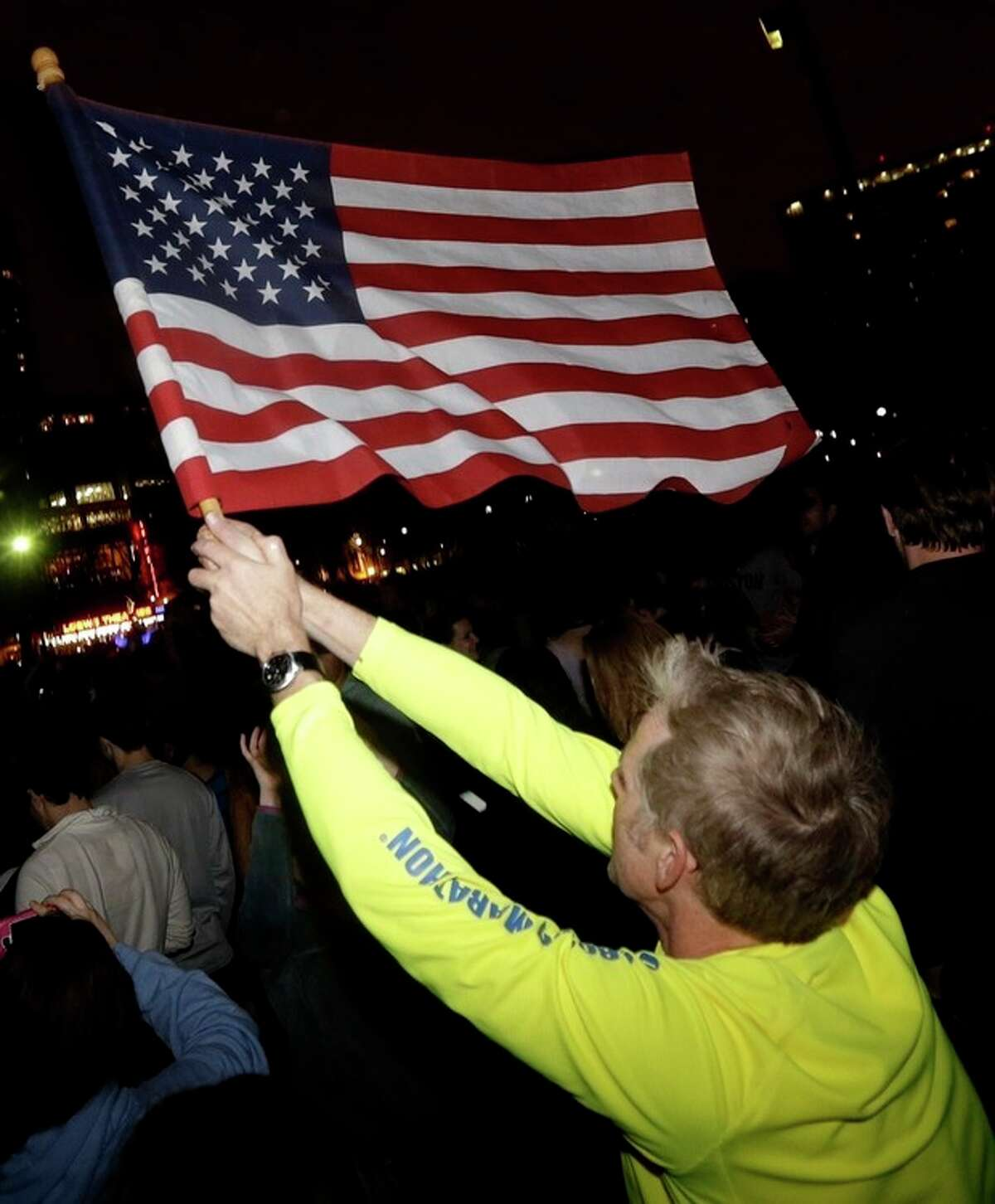 Frank McGillin, who ran three Boston Marathons, waves a U.S. flag as a crowd reacts to news of the arrest of one of the Boston Marathon bombing suspects during a celebration at Boston Common, Friday, April 19, 2013, in Boston. Boston Marathon bombing suspect Dzhokhar Tsarnaev was captured in Watertown, Mass. The 19-year-old college student wanted in the bombings was taken into custody Friday evening after a manhunt that left the city virtually paralyzed and his older brother and accomplice dead. (AP Photo/Julio Cortez)