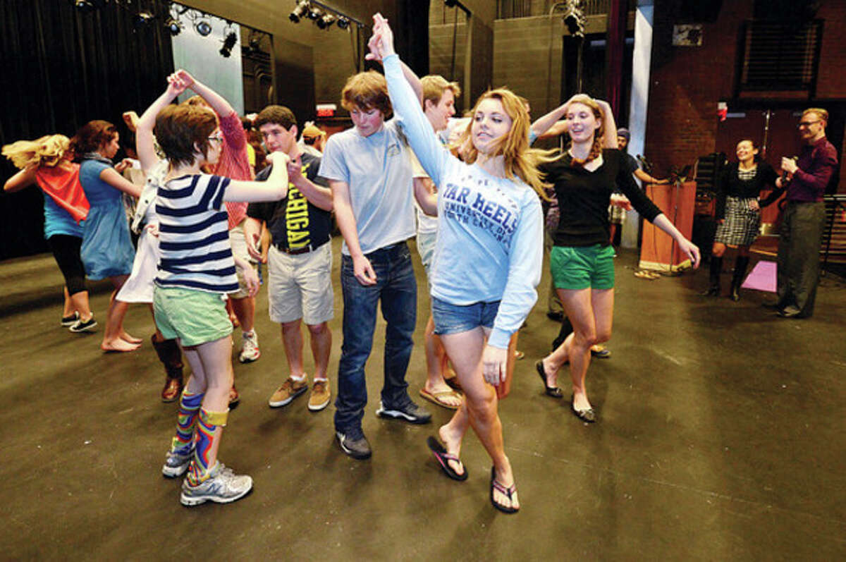 Wilton High School students including freshman Katie Litton, center, learn the Mrengue as part of the school's annual Festival of Languages Wednesday. Hour photo / Erik Trautmann