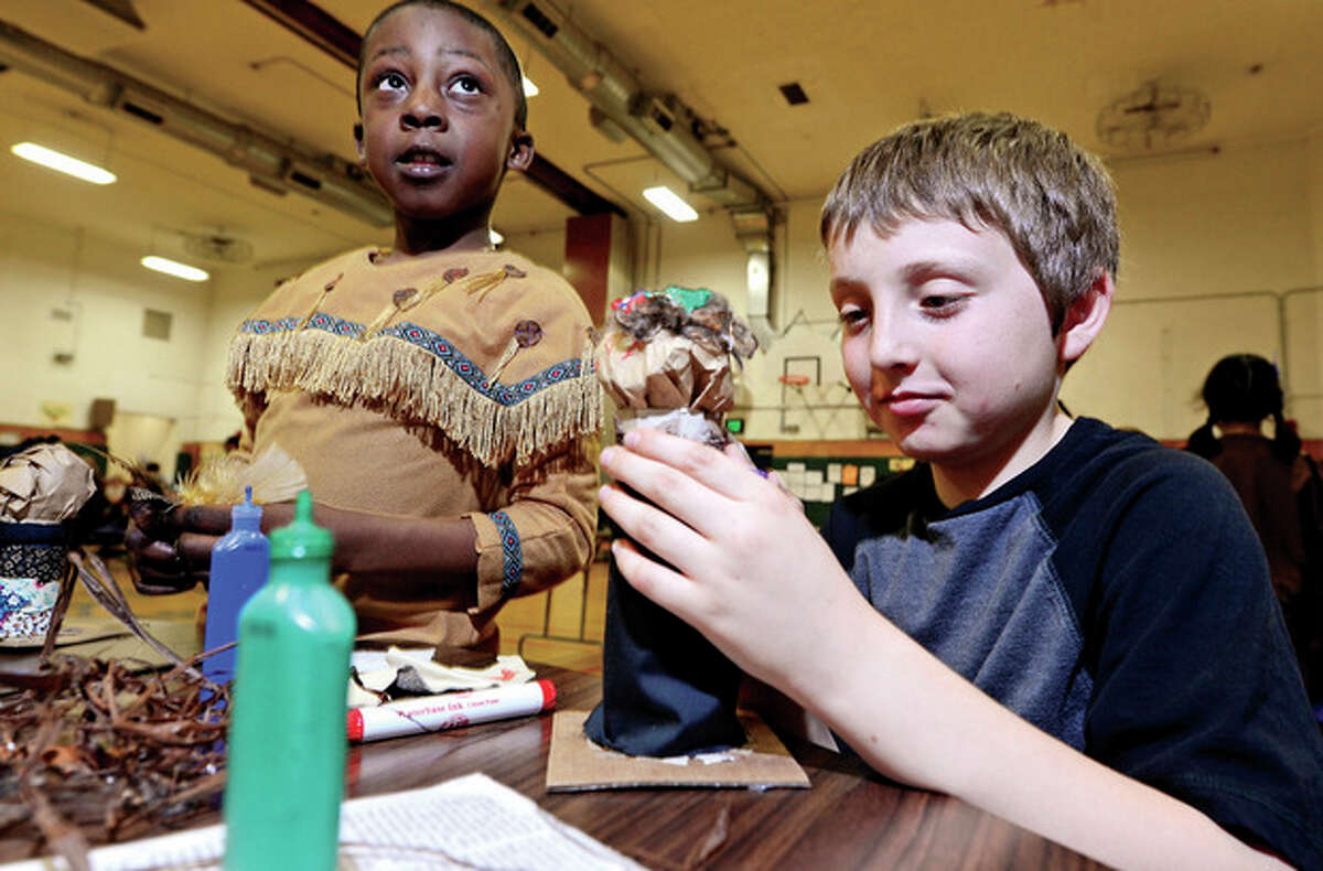 """Hour photo / Erik Trautmann Columbus Magnet School second grader, Terrell Holley shows 5th grader, Ian Asanovic, how to make an 'authentic"""" Native American craft during the school's Native American Day Wednesday. All craft supplies were donated by the LilySarahGraceFund.org whose founder, Matthew Badger tragically lost his daughters in the Christmas Eve fire in Stamford."""