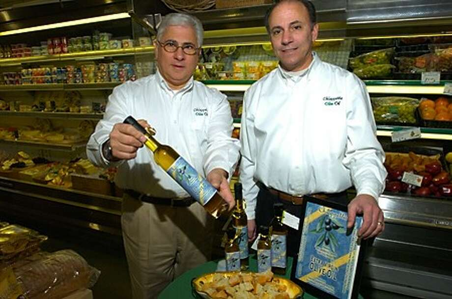 Pat and Frank Chiappetta give tastings of their extra virgin olive oil to patrons of the Rowayton Market Saturday. Hour photo / Erik Trautmann
