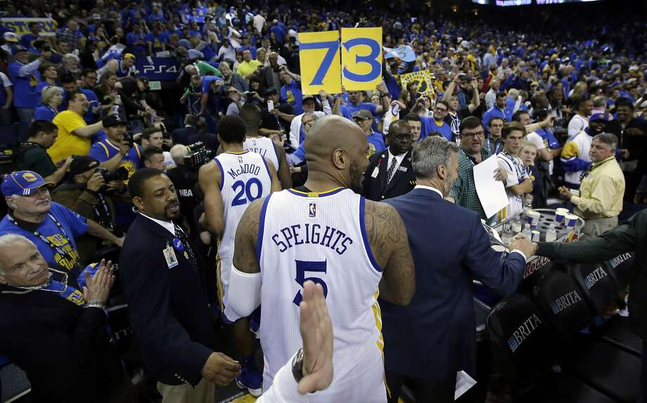 A 73 wins sign is held up as Golden State Warriors' Marreese Speights (5) and James Michael McAdoo (20) exit the court after a Warriors 125-104 win over the Memphis Grizzlies during an NBA basketball game Wednesday, April 13, 2016, in Oakland, Calif.  (AP Photo/Marcio Jose Sanchez) Photo: Marcio Jose Sanchez, AP
