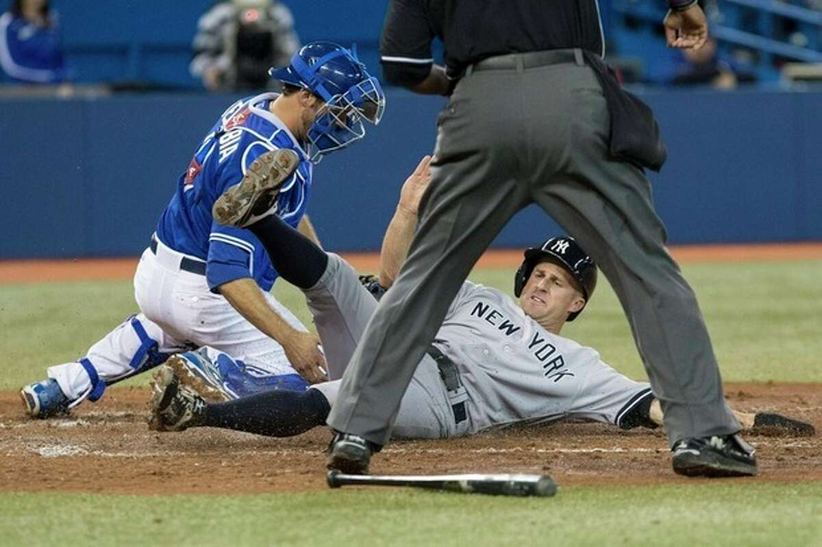New York Yankees' Brett Gardner slides safely into home in front of Toronto Blue Jays catcher J.P. Arencibia after a two-run single from Kevin Youkilis in the fifth inning of a baseball game in Toronto on Saturday, April 20, 2013. (AP Photo/The Canadian Press, Chris Young)
