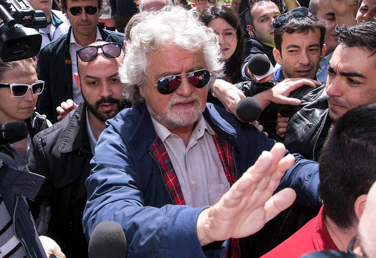 Comic-turned political agitator and leader of the anti-establishment 5 Star Movement Beppe Grillo arrives for a press conference in Rome, Sunday, April 21, 2013. Italy's Parliament on Saturday re-elected Giorgio Napolitano to an unprecedented second term as president, after party leaders persuaded the 87-year-old to serve again in hopes of easing the hostility that has thwarted formation of a new government. While Napolitano's election received a standing ovation from lawmakers and plaudits from abroad, several thousand people protested noisily outside Parliament Saturday, disappointed that Italy's old political guard hadn't changed. Lawmakers from Parliament's third-largest bloc, the anti-establishment 5 Star Movement led by comic-turned-political agitator Beppe Grillo, galvanized supporters for the protest. Grillo had backed a left-leaning constitutional law expert for president. Grillo and his fast-growing movement are bitterly opposed to the incumbent, who in late 2011 appointed Monti and a Cabinet of technocrats to replace an elected premier as the eurozone debt crisis threatened to engulf Italy. (AP Photo/Roberto Monaldo, Lapresse)