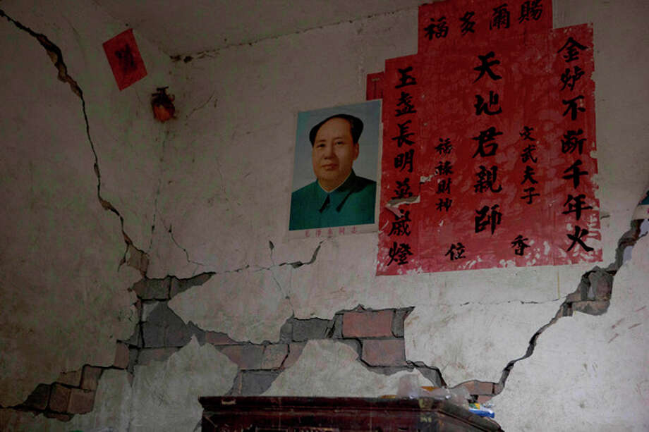 A portrait of Mao Zedong near writing commemorating Chinese ancestors is displayed on a wall damaged by Saturday's earthquake near Shangli town in southwestern China's Sichuan province, Sunday, April 21, 2013. The powerful earthquake that struck the steep hills of China's southwestern Sichuan province left at least 160 people dead and more than 6,700 injured. (AP Photo/Ng Han Guan) / AP