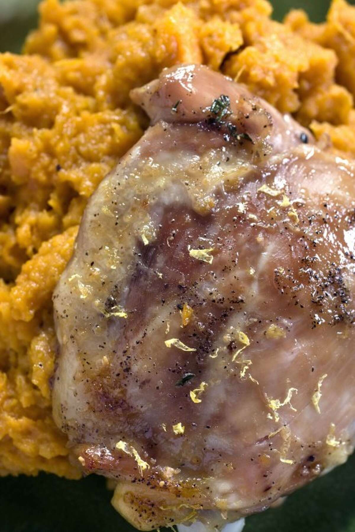 This Feb. 2, 2011 photo shows double maple roasted chicken thighs with sweet potatoes in Concord, N.H. If you have trouble finding granulated maple sugar, you can substitute an equal amount of dark brown sugar. (AP Photo/Larry Crowe)