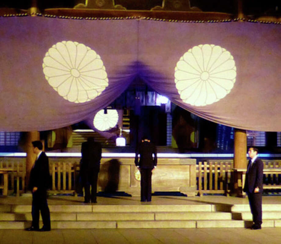 In this Sunday, April 21, 2013 photo, Japan's Deputy Prime Minister and Finance Minister Taro Aso, center right, bows as he visits the Yasukuni Shrine in Tokyo in the evening, following a visit by Keiji Furuya, state minister in charge of North Korea's past abductions of Japanese nationals, earlier in the day. Japan's Prime Minister Shinzo Abe made donations and three Cabinet ministers including Aso prayed at Tokyo's militarist shrine over the weekend, sparking South Korean anger. (AP Photo/Kyodo News) JAPAN OUT, MANDATORY CREDIT, NO LICENSING IN CHINA, HONG KONG, JAPAN, SOUTH KOREA AND FRANCE / Kyodo News