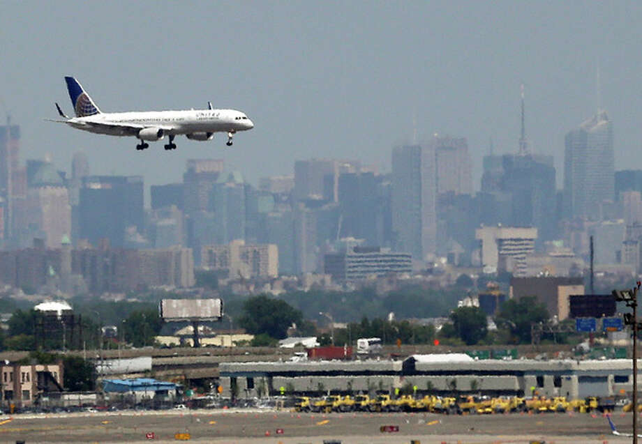 FILE - In this July 10, 2012 file photo, a United plane prepares to land at Newark Liberty International Airport in Newark, N.J., with the New York City skyline in the background. Commercial airline flights moved smoothly throughout most of the country on Sunday, April 21, 2013, the first day air traffic controllers were subject to furloughs resulting from government spending cuts, though some delays appeared in the late evening in and around New York. The real test, however, will come Monday, when traffic ramps up. (AP Photo/Julio Cortez, File) / AP
