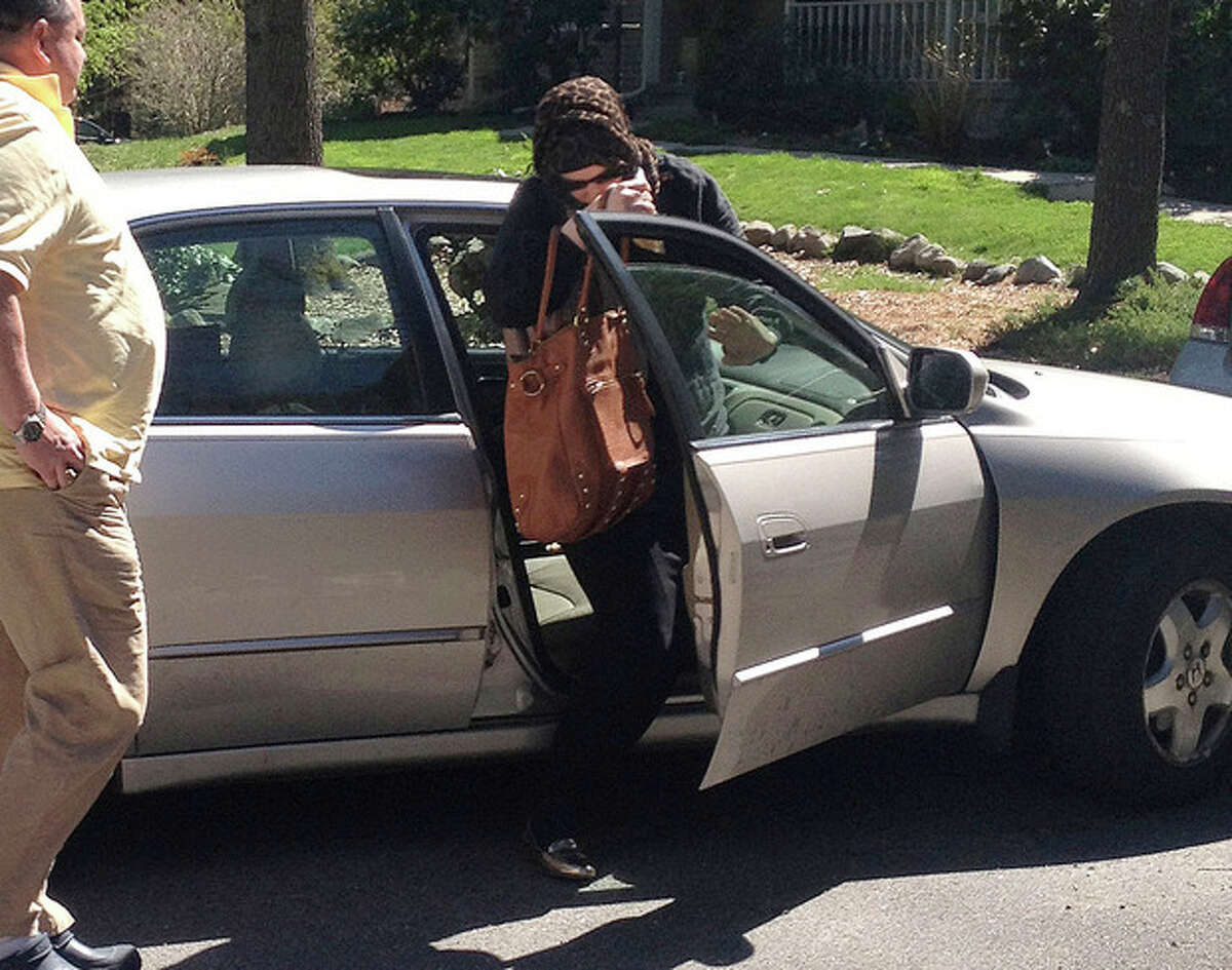 In this Sunday, April 21, 2013 photo, Katherine Russell Tsarnaev, center, wife of killed Boston Marathon bombing suspect Tamerlan Tsarnaev, exits a car at the home of her parents in North Kingstown, R.I. At left is her father, Warren Russell. Federal authorities have asked to speak with her, and her lawyer said he is discussing with them how to proceed. (AP Photo/Katie Zezima)