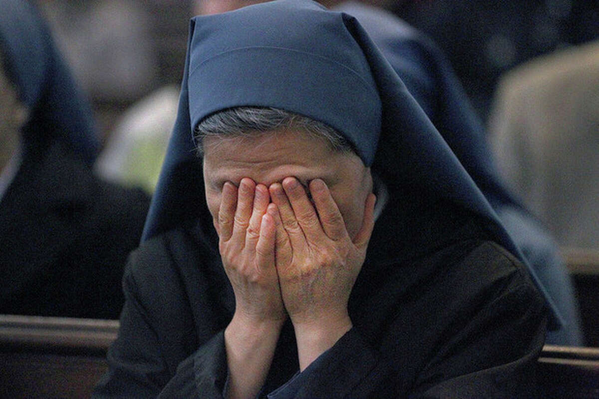 Sister Emmanuel, of the Sister Disciples of the Divine Master, prays before Mass at the Cathedral of the Holy Cross in Boston, on Sunday April 21, 2013. Prayers were said for the victims of the Boston Marathon bombings and the subsequent manhunt and first responders. (AP Photo/The Boston Globe, Pat Greenhouse)
