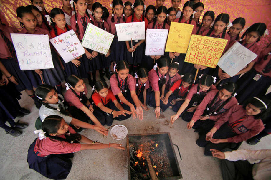 Indian schoolgirls perform rituals as they offer prayers for the speedy recovery of a 5-year-old girl who was raped and tortured in New Delhi, at Dewan Devi Public School in Jammu, India, Monday, April 22, 2013. A second suspect was arrested Monday in the rape of the girl who New Delhi police said was left for dead in a locked room, a case that has brought a new wave of protests against how Indian authorities handle sex crimes. (AP Photo/Channi Anand) / AP