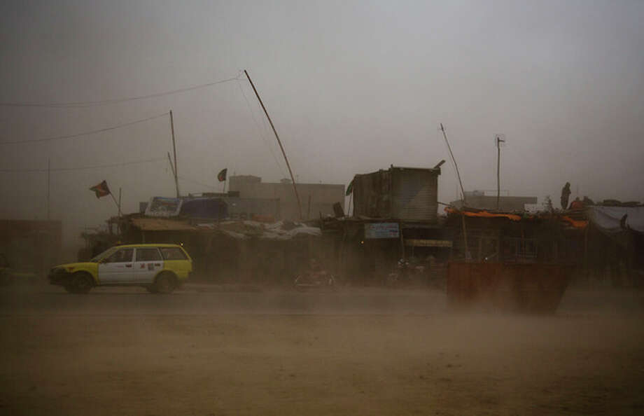 A taxi tries to make its way through a sandstorm that obscures the city of Kanadahar, Afghanistan, Sunday April 21, 2013. (AP Photo/Anja Niedringhaus) / AP