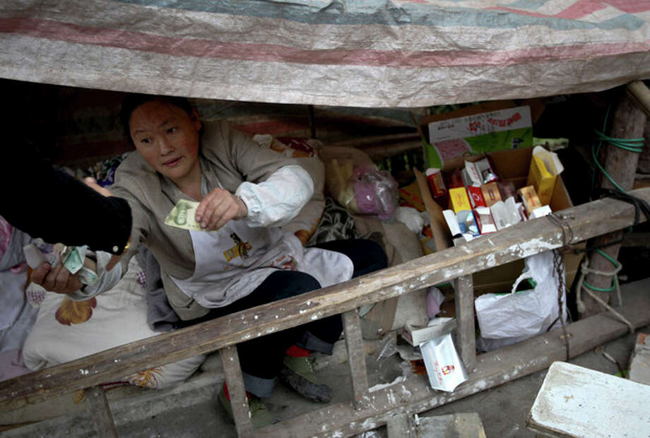 A woman opens business in a shelter near her damaged shop after the earthquake in Yuxi village of Baosheng township in Lushan county in southwest China's Sichuan province Sunday, April 21, 2013. Saturday's earthquake in Sichuan province killed over 200 people, China's Xinhua News Agency said. (AP Photo) CHINA OUT / CHINATOPIX