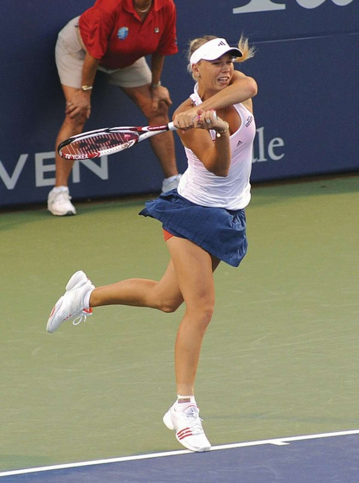 Hour photo/John Nash Top-seeded Caroline Wozniacki rifles a shot at Francesa Schiavone during Friday night's second semifinal at the New Haven Open. Wozniacki won, 7-6 (2) 6-3, and will face Czech qualifier Petra Cetkovska in today's championship match.