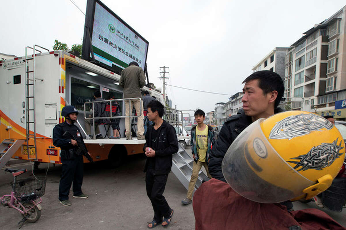 A armed security person guards a mobile bank in the earthquake struck county seat of Lushan in southwestern China's Sichuan province, Monday, April 22, 2013. China's full range of disaster response in the aftermath of Saturday's earthquake is on display: Trucks with x-ray equipment, phone-charging stations, bank tellers-on-wheels - even a tent for insurance claims. (AP Photo/Ng Han Guan)