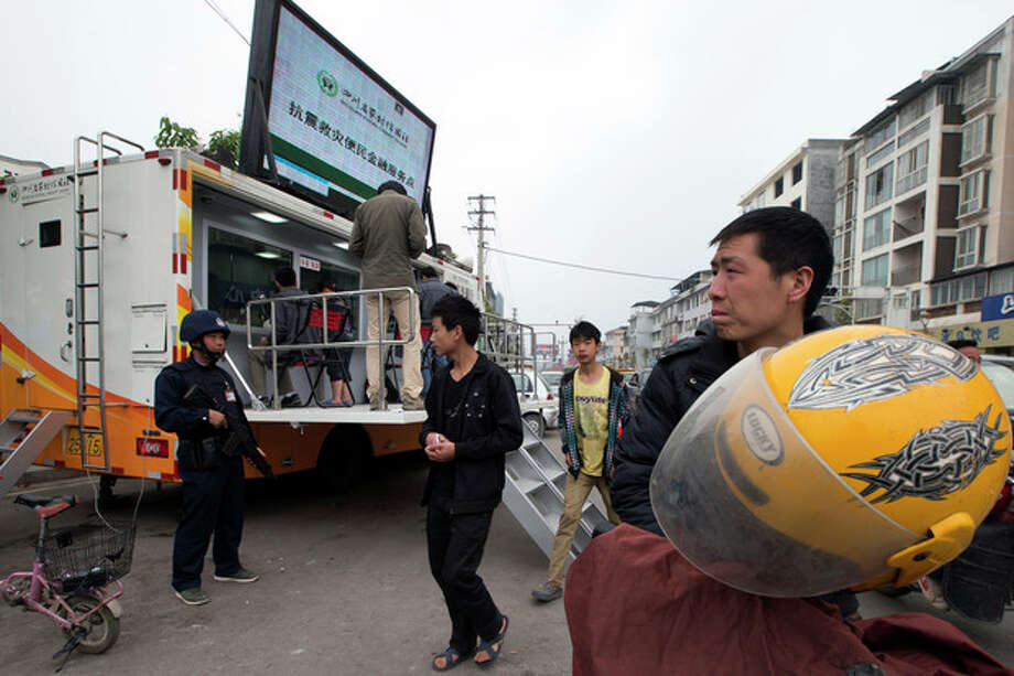 A armed security person guards a mobile bank in the earthquake struck county seat of Lushan in southwestern China's Sichuan province, Monday, April 22, 2013. China's full range of disaster response in the aftermath of Saturday's earthquake is on display: Trucks with x-ray equipment, phone-charging stations, bank tellers-on-wheels - even a tent for insurance claims. (AP Photo/Ng Han Guan) / AP