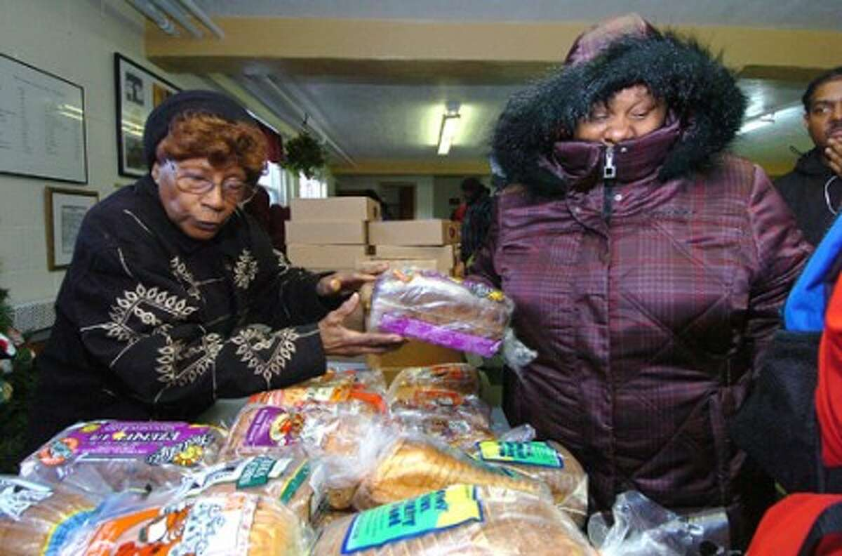 Photo/Alex von Kleydorff. Mother Louise Montgomery helps people get loaves of bread at the Wilson Food Panrty.