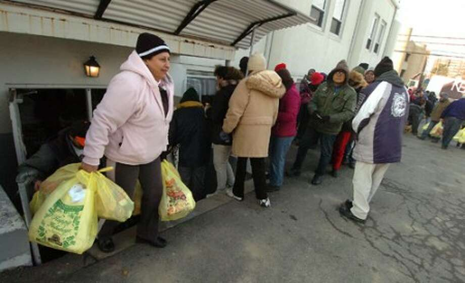 Photo/Alex von Kleydorff. People leave the Wilson Food Pantry with much needed bags of food as others wait their turn in line.