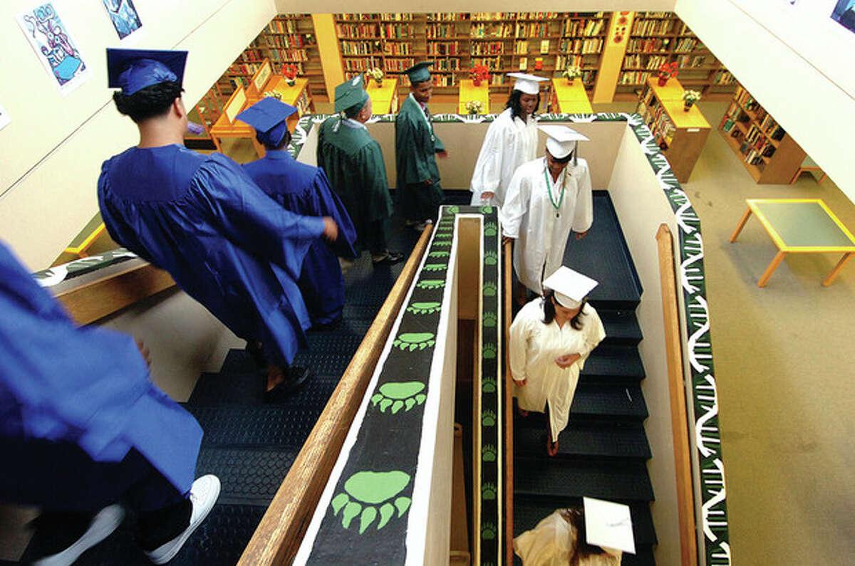 Hour photo / Alex von Kleydorff Graduates make their way down the steps of the Norwalk High School Library.