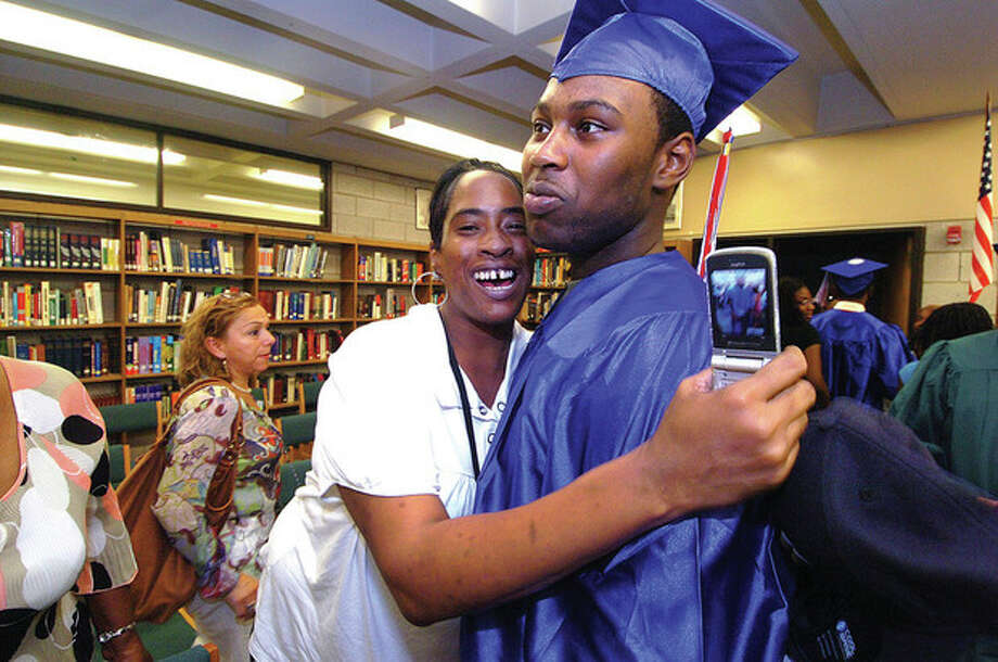 Brien McMahon Graduate Lamar Tate gets a hug from his Aunt Joyce Tate as he has his diploma in hand. / 2011 The Hour Newspapers