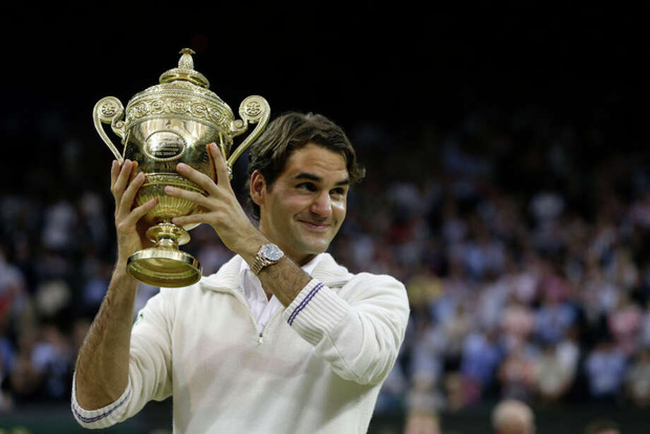 Roger Federer of Switzerland celebrates with the trophy after winning the men's singles final against Andy Murray of Britain at the All England Lawn Tennis Championships at Wimbledon, England, Sunday, July 8, 2012. (AP Photo/Kirsty Wigglesworth) / AP