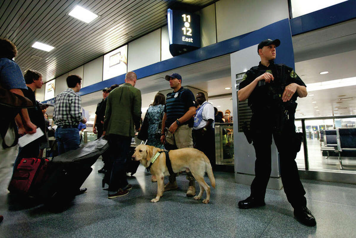 Amtrack police officers stand guard while commuters get ready to board their train in New York Pennsylvania Station on Friday, Sept. 9, 2011 in New York. The city is deploying additional resources and taking other security steps in response to a potential terror threat before the 10th anniversary of the Sept. 11 attacks. U.S. counterterrorism officials are chasing a credible but unconfirmed al-Qaida threat to use a car bomb on bridges or tunnels in New York or Washington. (AP Photo/Jin Lee)