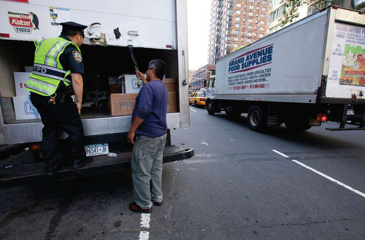 A New York City police officer examines a delivery truck at a vehicle check point on Friday, Sept. 9, 2011 in New York. The city is deploying additional resources and taking other security steps in response to a potential terror threat before the 10th anniversary of the Sept. 11 attacks. U.S. counterterrorism officials are chasing a credible but unconfirmed al-Qaida threat to use a car bomb on bridges or tunnels in New York or Washington. (AP Photo/Jin Lee)