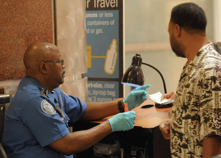 Airline passengers have their identifications checked while passing through the Transportation Security Administration security checkpoint at Hartsfield-Jackson Atlanta International Airport on Wednesday August 3, 2011 in Atlanta. The TSA was created after the terrorist attacks of Sept. 11, 2001. (AP Photo/Erik S. Lesser) / FR53108 AP