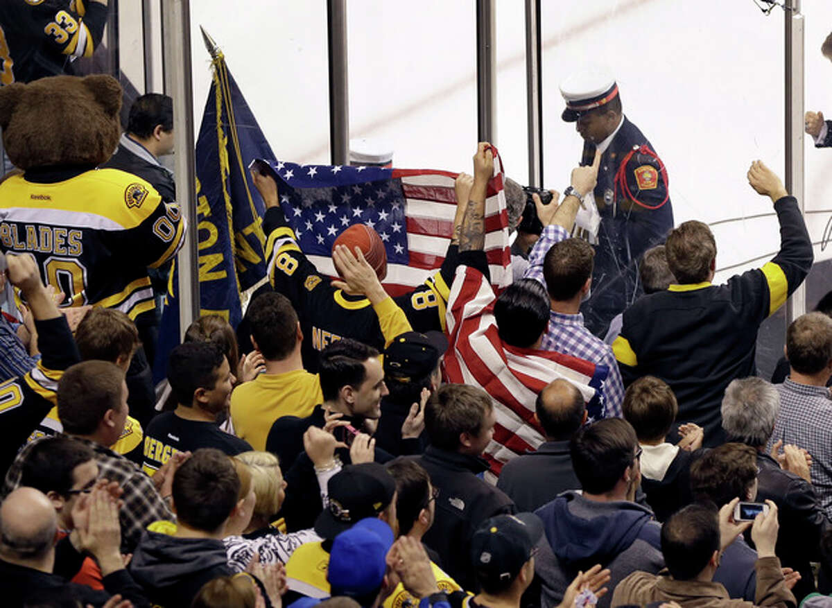 Fans react with flags after the singing of the national anthem at TD Garden in Boston, Wednesday, April 17, 2013, during a pregame ceremony in the aftermath of Monday's Boston Marathon bombings. (AP Photo/Elise Amendola)