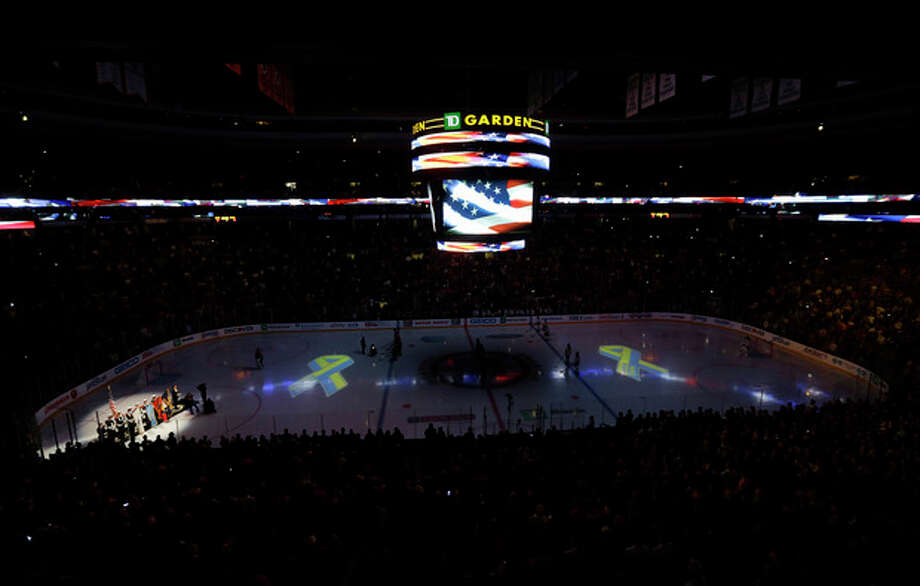 Members of a Boston Fire Department honor guard hold flags during the singing of the national anthem at TD Garden in Boston, Wednesday, April 17, 2013, during a pregame ceremony in the aftermath of Monday's Boston Marathon bombings. (AP Photo/Elise Amendola) / AP