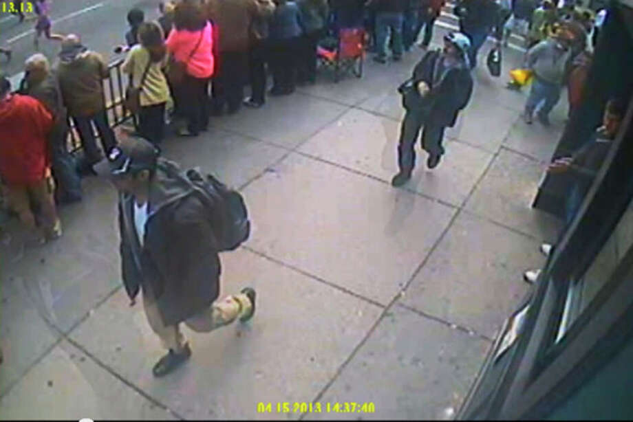 This image taken from video released by the FBI on Thursday, April 18, 2013 shows what the FBI are calling suspect number 1, front, in black cap, and suspect number 2, in white cap, back right, walking near each other through the crowd in Boston on Monday, April 15, 2013, before the explosions at the Boston Marathon. (AP Photo/FBI) / FBI