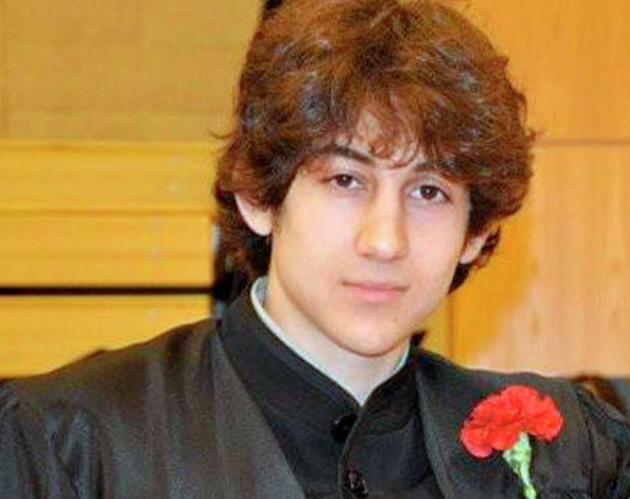 In this undated photo provided by Robin Young, Dzhokhar A. Tsarnaev, poses for a photo after graduating from Cambridge Rindge and Latin High School. Tsarnaev has been identified as the surviving suspect in the marathon bombings. Two suspects in the Boston Marathon bombing killed an MIT police officer, injured a transit officer in a firefight and threw explosive devices at police during a getaway attempt in a long night of violence that left one of them dead and another still at large Friday, April 19, 2013. (AP Photo/Robin Young) / Here And Now