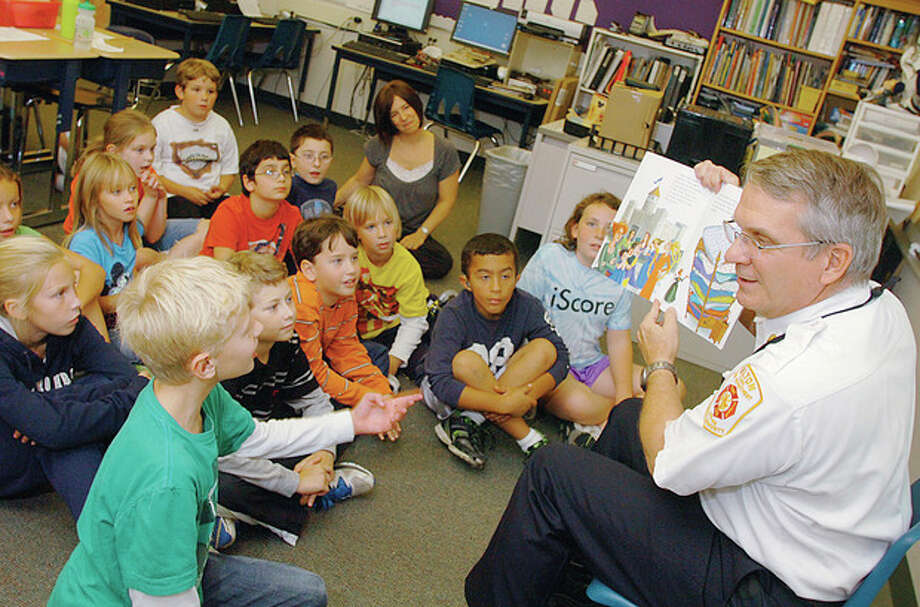 Wilton Fire Chief Paul Milositz reads the Princess and the PIzza to Ms. Jodi Luongo's 4th grade class at Cider Mill School Tuesday as part of the Read Aloud Day. Hour photo / Erik Trautmann / (C)2011, The Hour Newspapers, all rights reserved