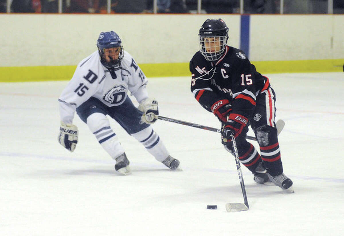 Hour photo/John Nash New Canaan's Dylan Hart tries to find some shooting room as he is stalked by Darien defender Nick Bruno during Monday's game at the Darien Ice Rink. The Blue Wave skated to a 6-1 victory in the matchup of longtime rivals.
