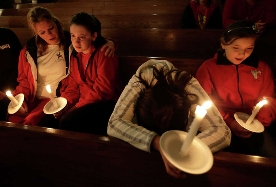 Mourners attend a service at St. Mary's Church of the Assumption Thursday, April 18, 2013, a day after an explosion at a fertilizer plant in West, Texas. The massive explosion at the West Fertilizer Co. Wednesday night killed as many as 15 people and injured more than 160. (AP Photo/Charlie Riedel) / AP