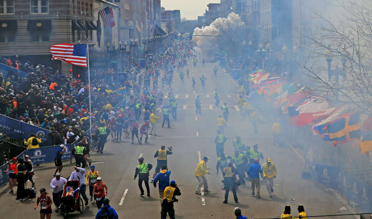 FILE - In this Monday, April 15, 2013 file photo, people react as an explosion goes off near the finish line of the 2013 Boston Marathon in Boston. Event after nail-biting event, America was rocked this week, in rare and frightening ways, with what felt like an unremitting series of tragedies. (AP Photo/The Boston Globe, David L Ryan, File) MANDATORY CREDIT: THE BOSTON GLOBE, DAVID L RYAN