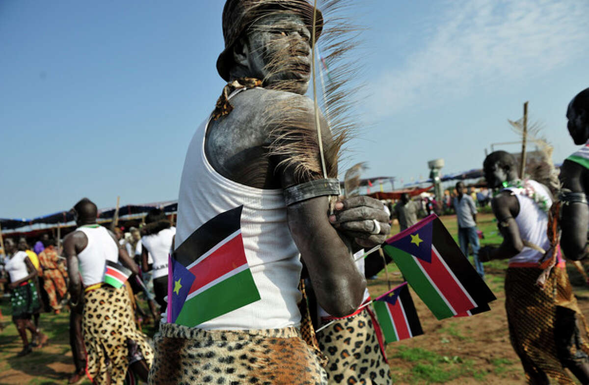 AP Photo/Shannon Jensen A man holds South Sudanese flags as he prepares to dance at the country's anniversary celebrations, at the John Garang mausoleum in Juba, South Sudan, Monday, July 9.