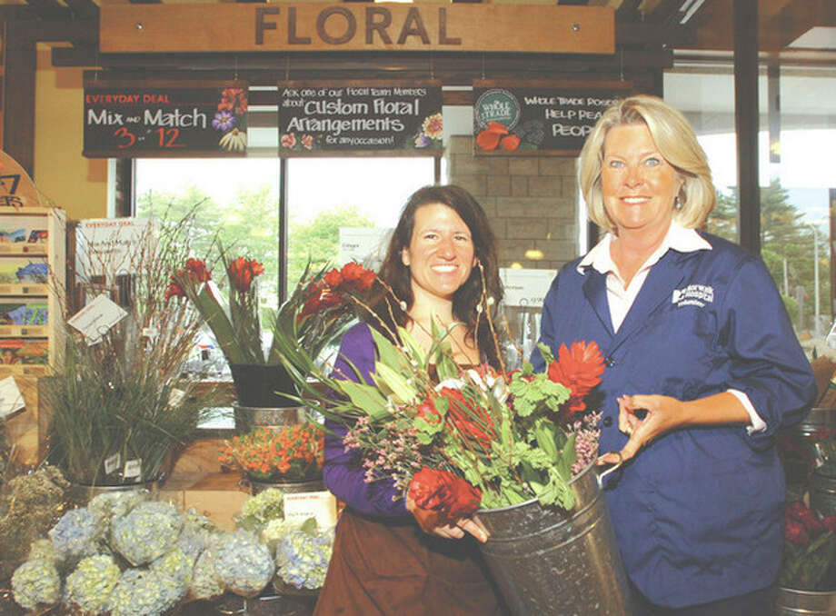 Contributed photoNorwalk Hospital volunteer LaVonne Kramer, right, receives flowers from Melissa Trombetto with Whole Foods Market in Westport for the Flowers for Patients program that Kramer started at Norwalk Hospital. / ©2012 The Hour Newspapers