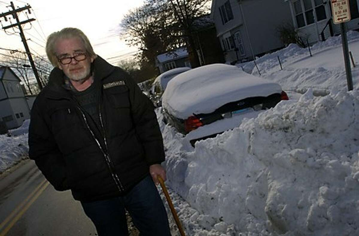Kevin Fitzgerald compalined to the city for plowing piles of snow on the corner of Osborne and Fort Point St. trapping his car. Hour photo / Erik Trautmann