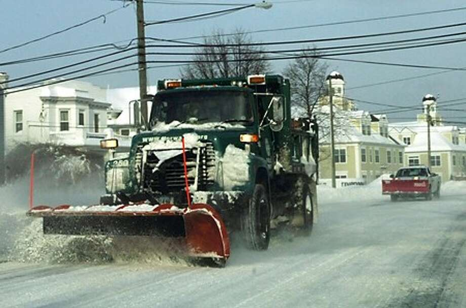 A Norwalk city plow takes snow off East Ave. Hour photo / Erik Trautmann
