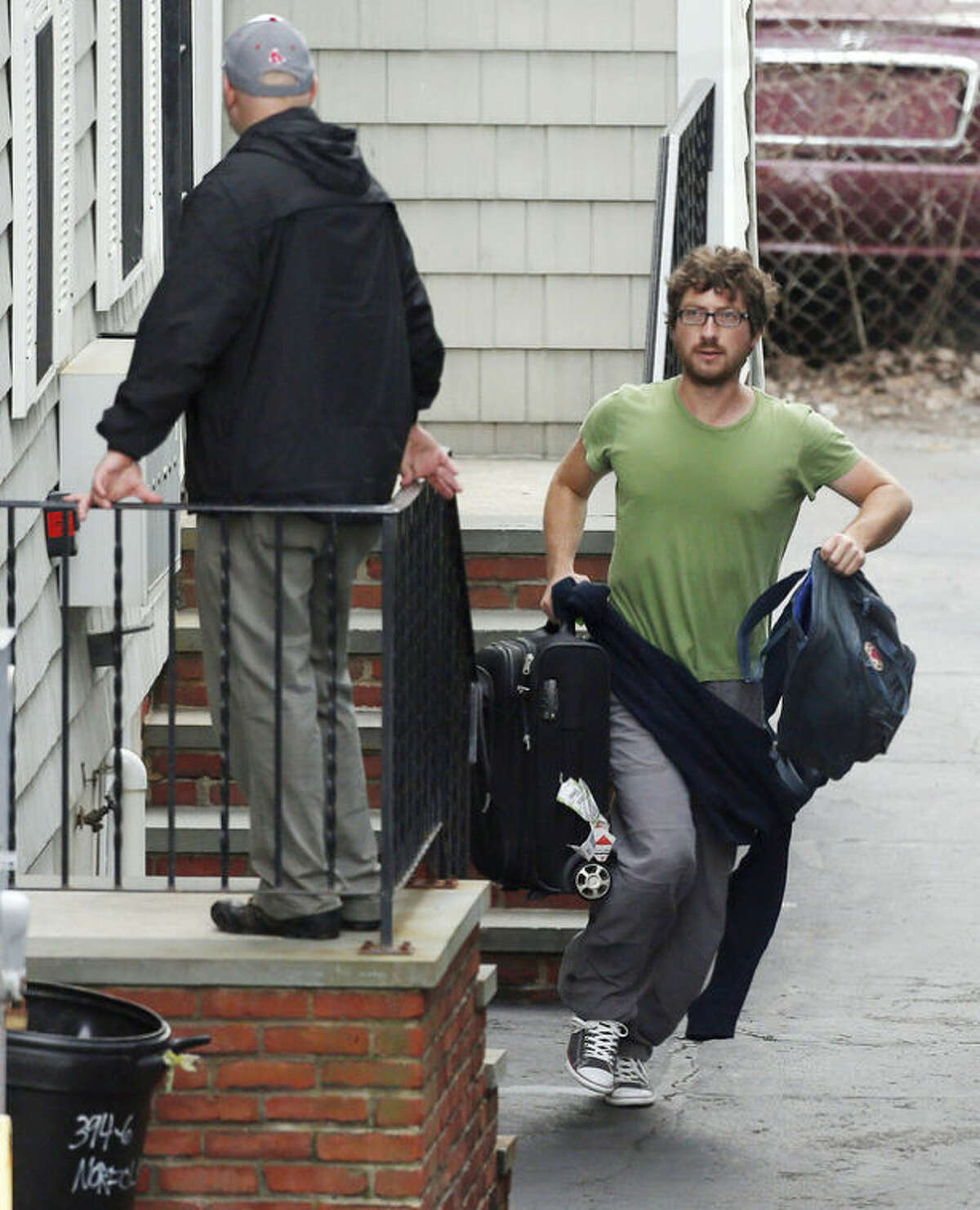 A resident evacuates as police go door-to-door on Norfolk Street in search of a suspect in the Boston Marathon bombings in Cambridge, Mass., Friday, April 19, 2013. Two suspects in the Boston Marathon bombing killed an MIT police officer, injured a transit officer in a firefight and threw explosive devices at police during a getaway attempt in a long night of violence that left one of them dead and another still at large Friday, authorities said as the manhunt intensified for a young man described as a dangerous terrorist.(AP Photo/Michael Dwyer)
