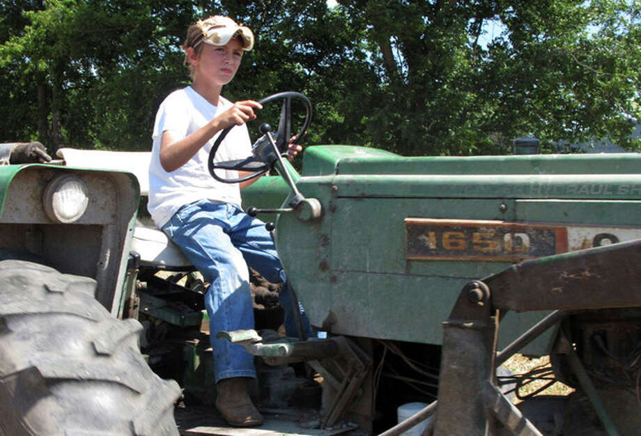 In a June 20, 2012, photo ten-year-old Jacob Mosbacher guides a tractor through a bean field on his grandparents' property near Fults, Ill. Agriculture organizations and federal lawmakers from farm states succeeded last spring in convincing the U.S. Labor Department to drop proposals limiting farm work by children such as Jacob, whose parents say such questions of safety involving kids should be left to parents. (AP Photo/Jim Suhr) / AP