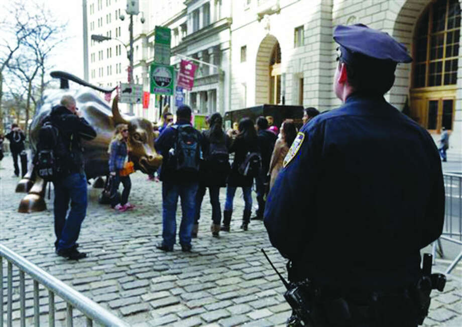 A New York City Police officer watches as people take pictures with the bull statue in the Financial District, Tuesday, April 16, 2013 in New York. Law enforcers say New York City remains in a heightened state of alert until more is known about the Boston explosions. More officers are working around New York, including counterterrorism units and beefed up patrols.