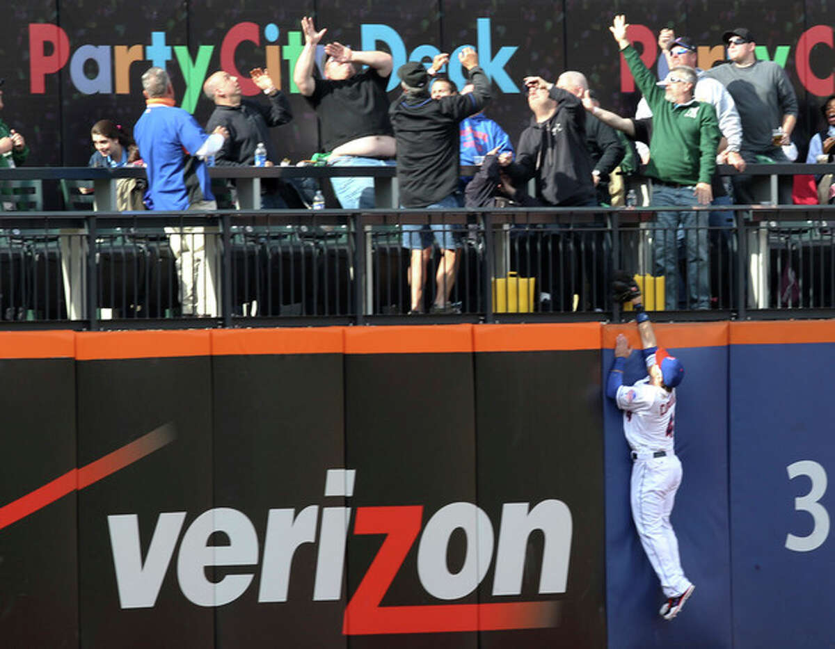 New York Mets center fielder Collin Cowgill leaps against the wall as a three-run home run by Washington Nationals' Adam LaRoche lands in the stands in the fifth inning of a baseball game in New York on Saturday, April 20, 2013. (AP Photo/Peter Morgan)